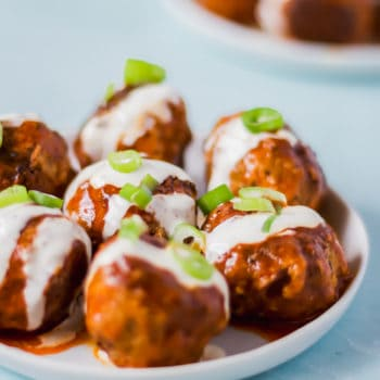 buffalo turkey meatballs on a white plate drizzled with ranch dressing and topped with green onions against a blue background