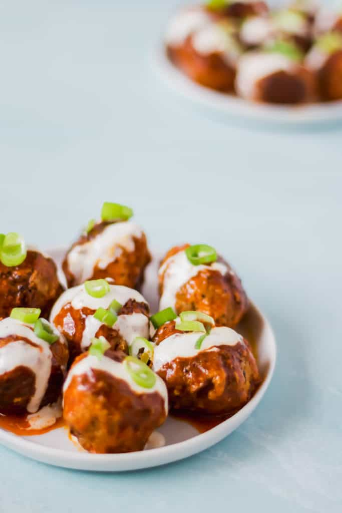 buffalo turkey meatballs arranged on two white plates with ranch dressing and green onions