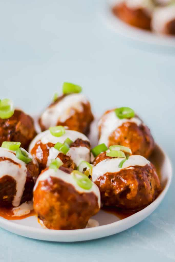 orange colored buffalo turkey meatballs drizzled with white liquid and topped with green onions