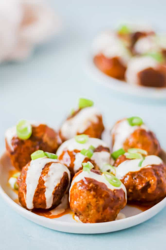 orange colored buffalo turkey meatballs on a white plate with white ranch dressing and green onions on top with a blue background and white napkin