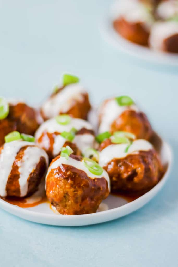 seven buffalo turkey meatballs arranged on a white plate drizzled with white ranch dressing and green onion on a light blue background