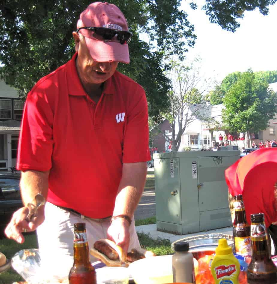 man in a red wisconsin polo shirt building his brat at an outdoor tailgate