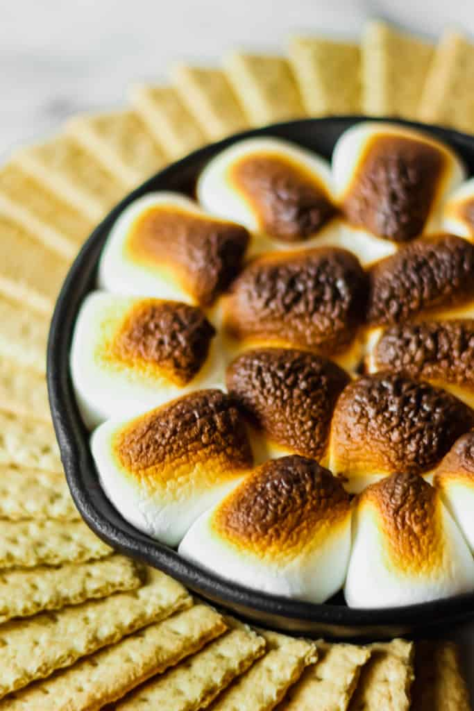 graham crackers in a circle surrounding a cast iron skillet filled with browned marshmallows