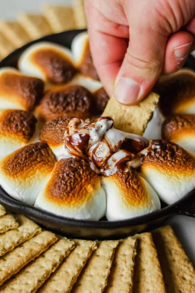 a person holding a graham cracker dipping it into a cast iron filled with browned marshmallows