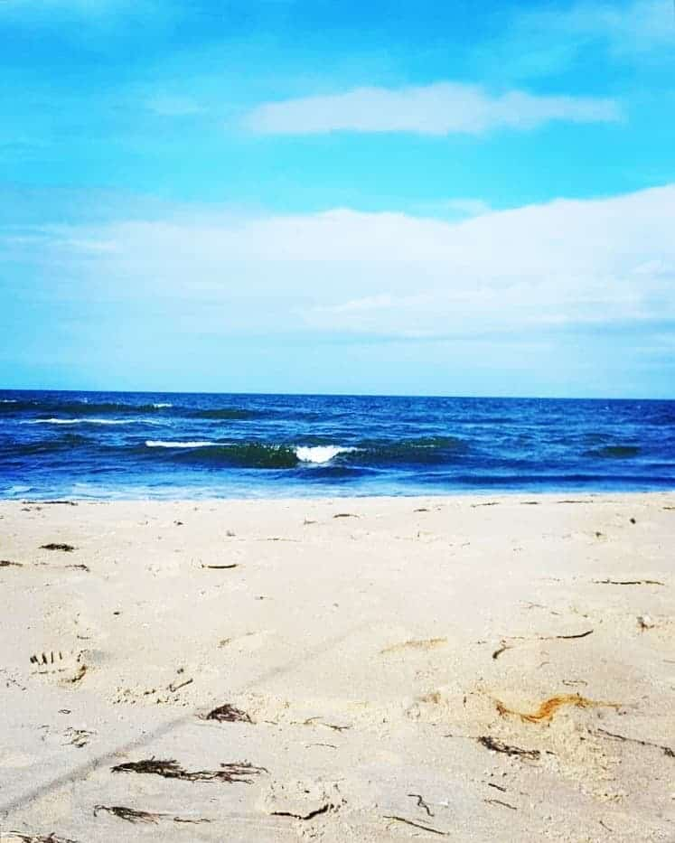 footprints in the white sand and a wave curling in the blue ocean at the outer banks