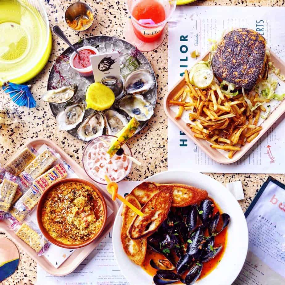 mussels, burger, oysers and cocktails on a table with hello sailor menus