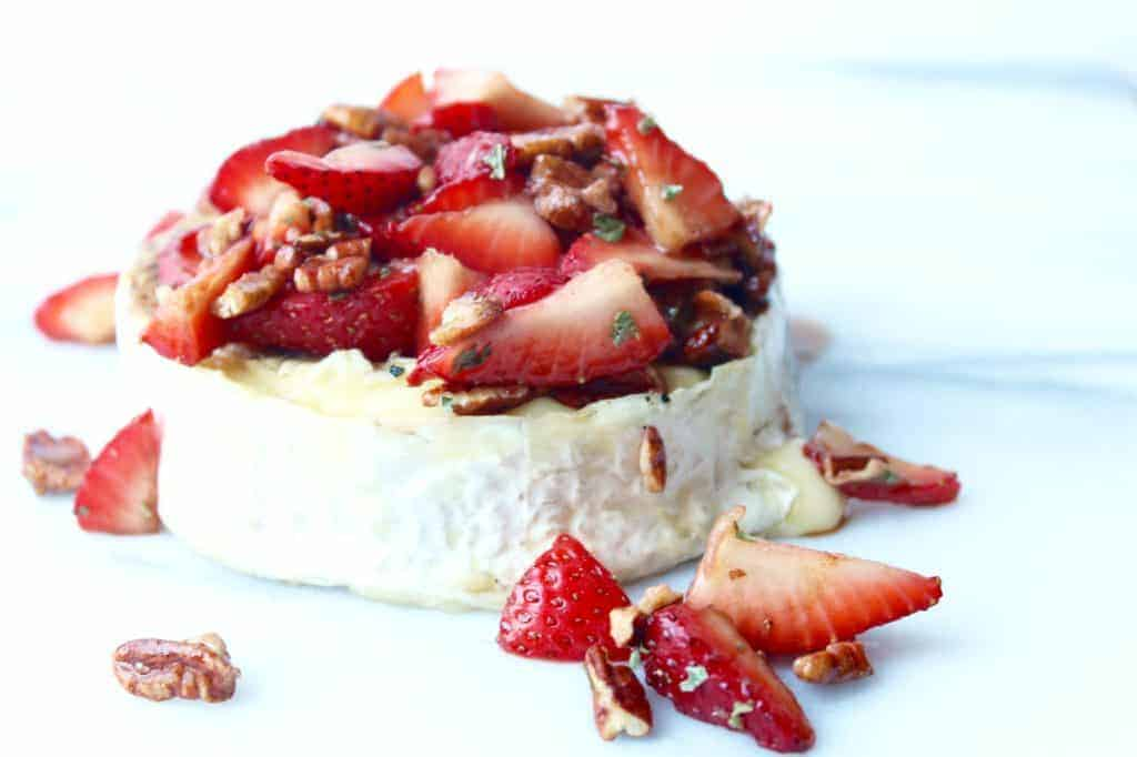 easy brie appetizer with strawberries and pecans on a white background