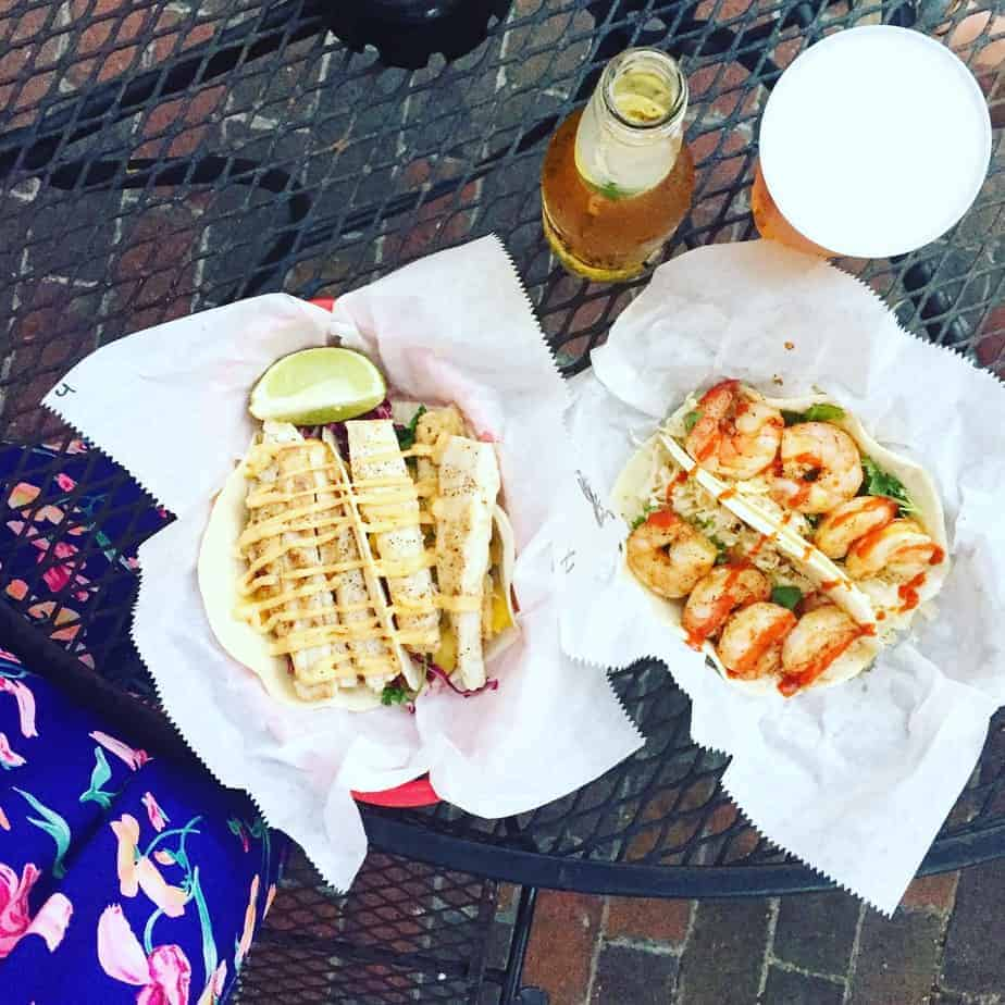 two baskets filled with fish tacos and shrimp tacos on a black table with a glass of beer and bottle of beer on the side