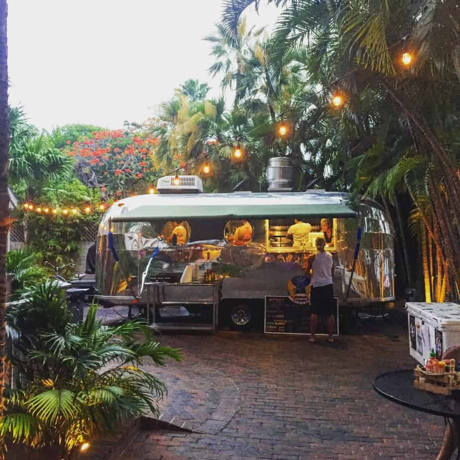 silver airstream trailer on a brick patio surrounded with cafe lights and palm trees in key west, florida