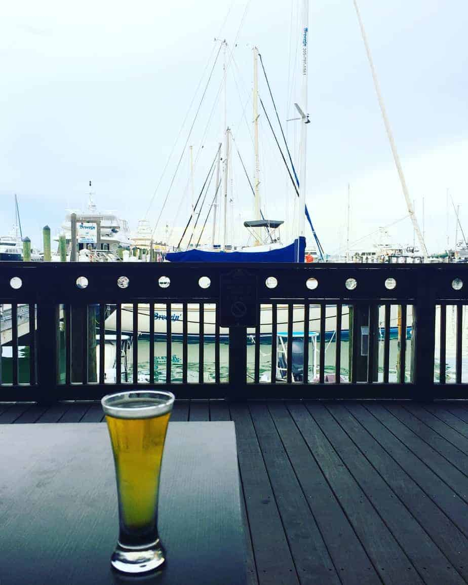 pint of beer on a patio table with sailboats in the background