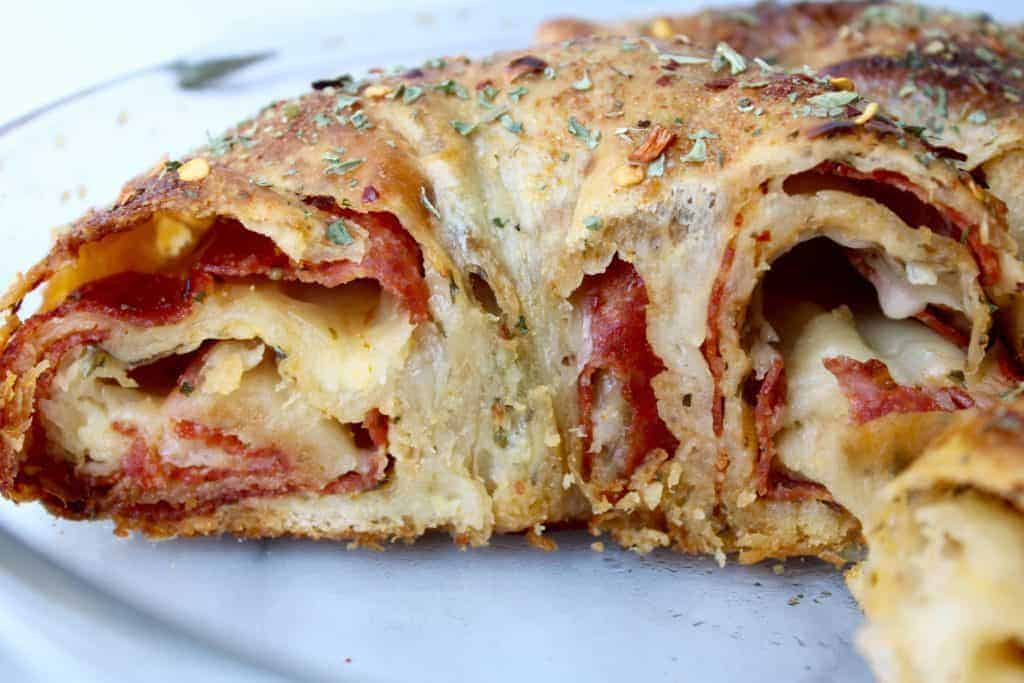 pepperoni stuffed bread with cheese and spices in a glass pie plate