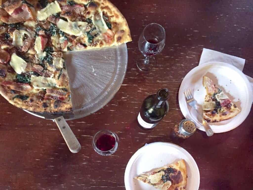 sharing a wine bottle and some pizza at elkin creek vineyards