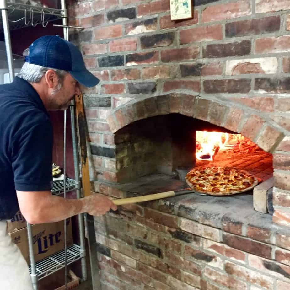 putting pizza in the wood fire oven at elkin creek vineyard, a north carolina winery