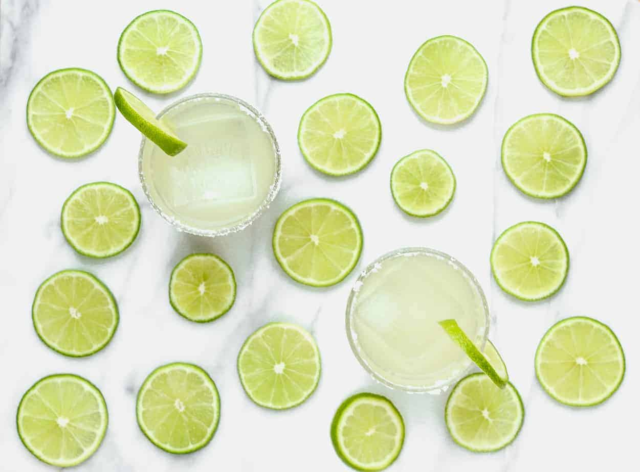 two classic margaritas with ice cubes and limes