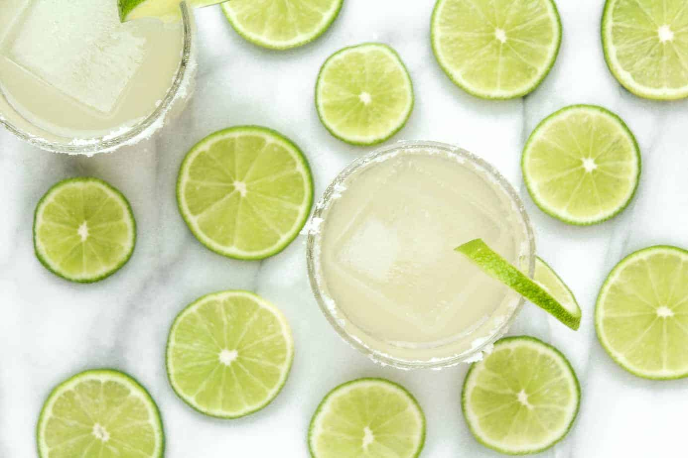 classic margaritas on a marble countertop with limes