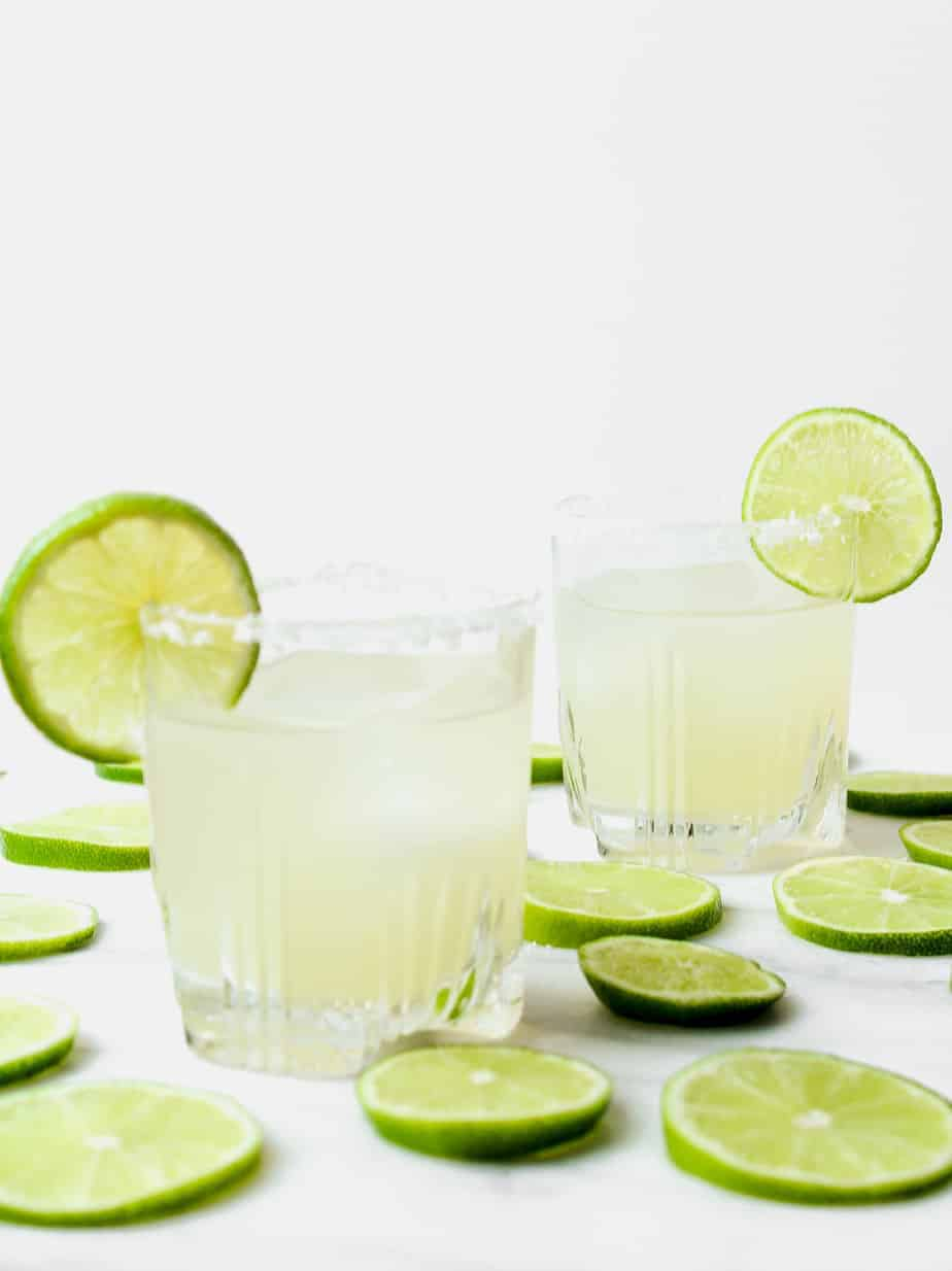two classic margaritas with lime wheels