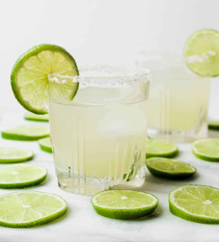 two classic margaritas with salt rimmed glasses and lime garnish surrounded by limes