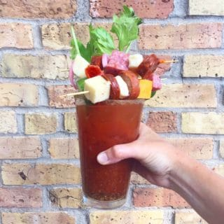 bloody mary with cheese sausage celery vegetables in front of a brick wall