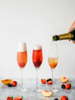 three champagne flutes filled with fruit puree and champange on a marble background with fruit