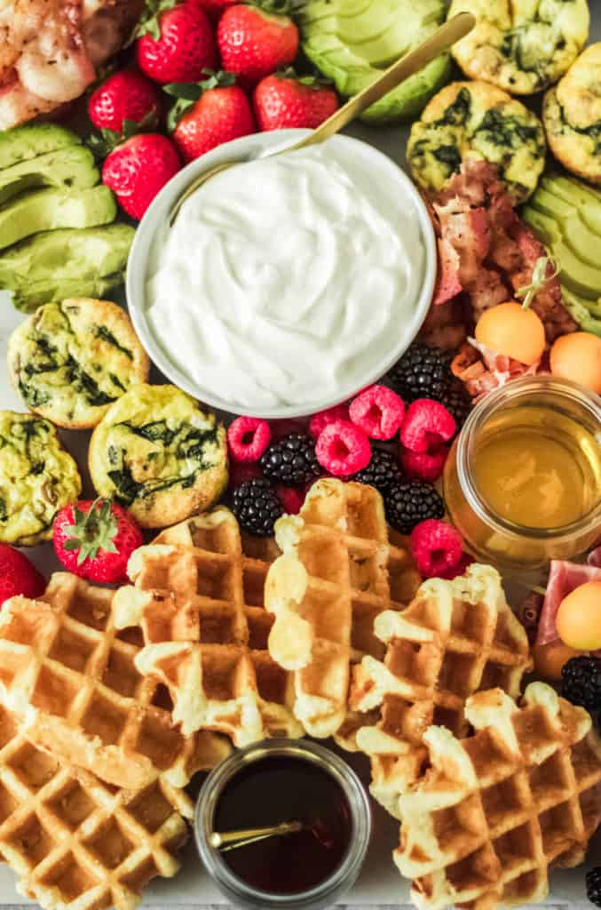 brunch board made with waffles, maple syrup, honey, egg muffins, raspberries and blackberries, greek yogurt, bacon and avocado