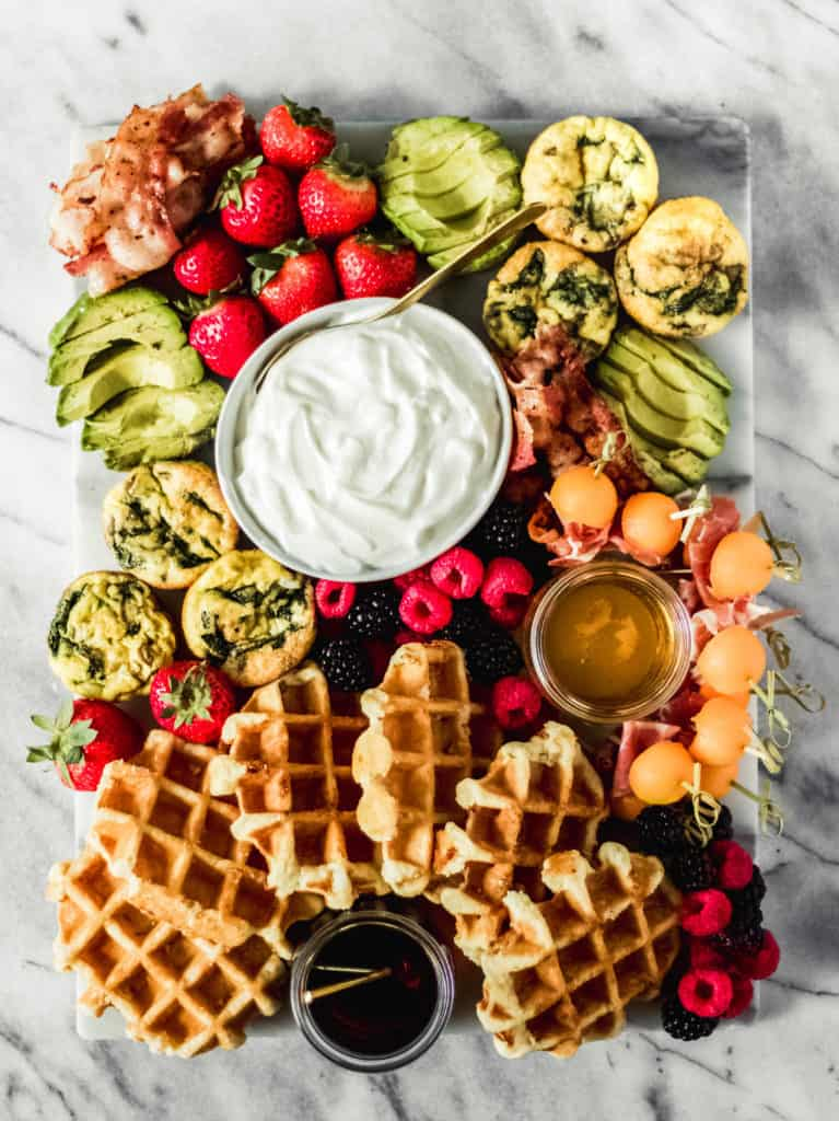 waffle themed brunch board with syrup, fresh fruit, avocado and eggs on a marble background