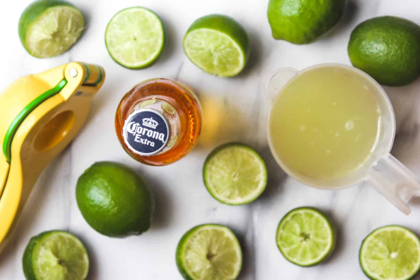 lime juice, limes and corona extra on a marble platter
