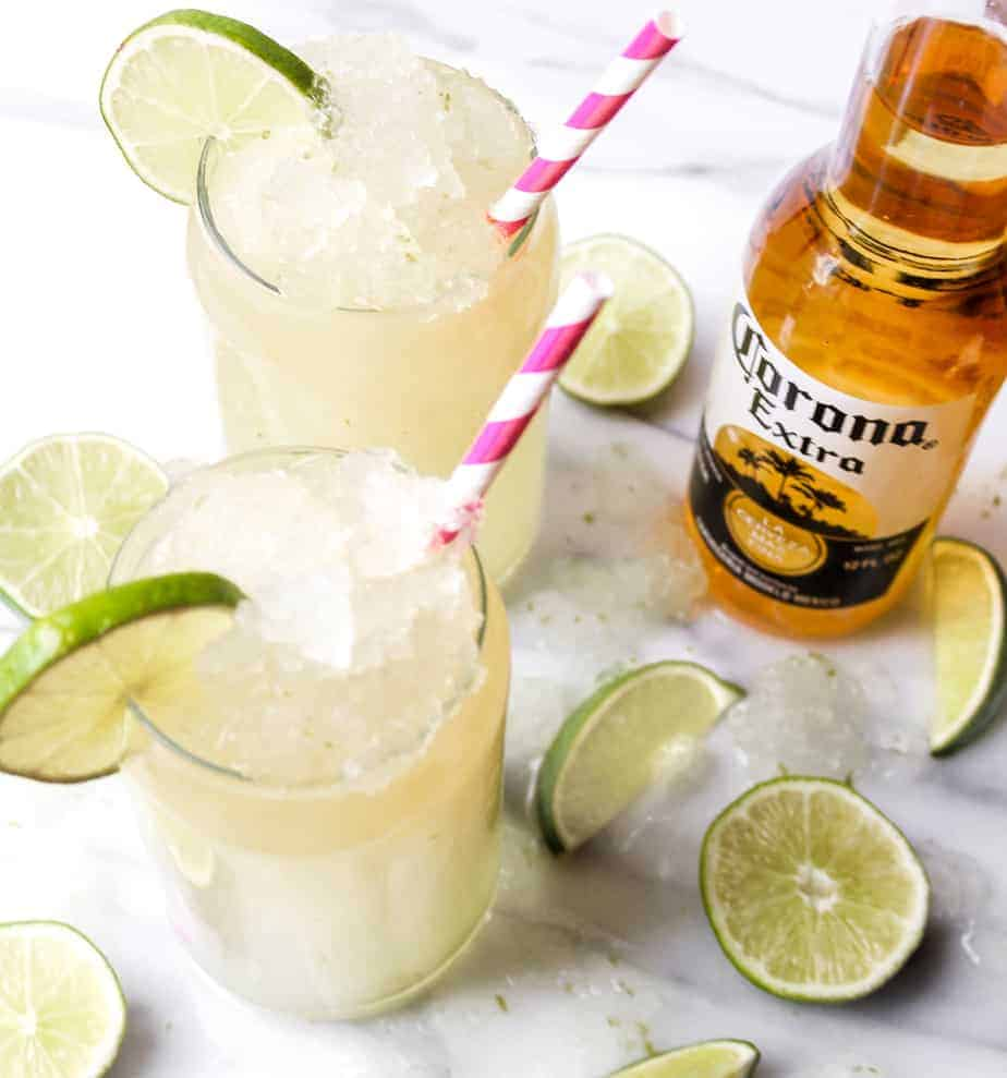 bottle of corona extra with two corona cocktails in glasses with ice and lime