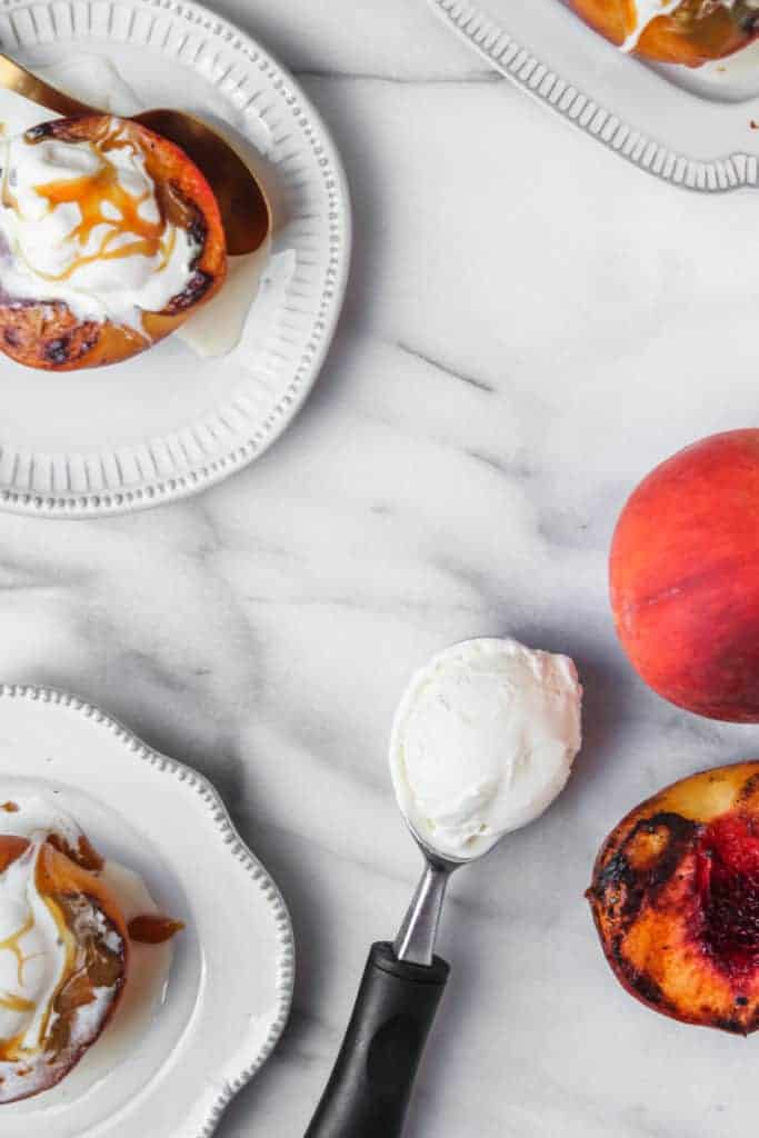 grilled peach halves made into sundaes with melted vanilla ice cream on white plates with an ice cream scoop, ice cream and whole peaches