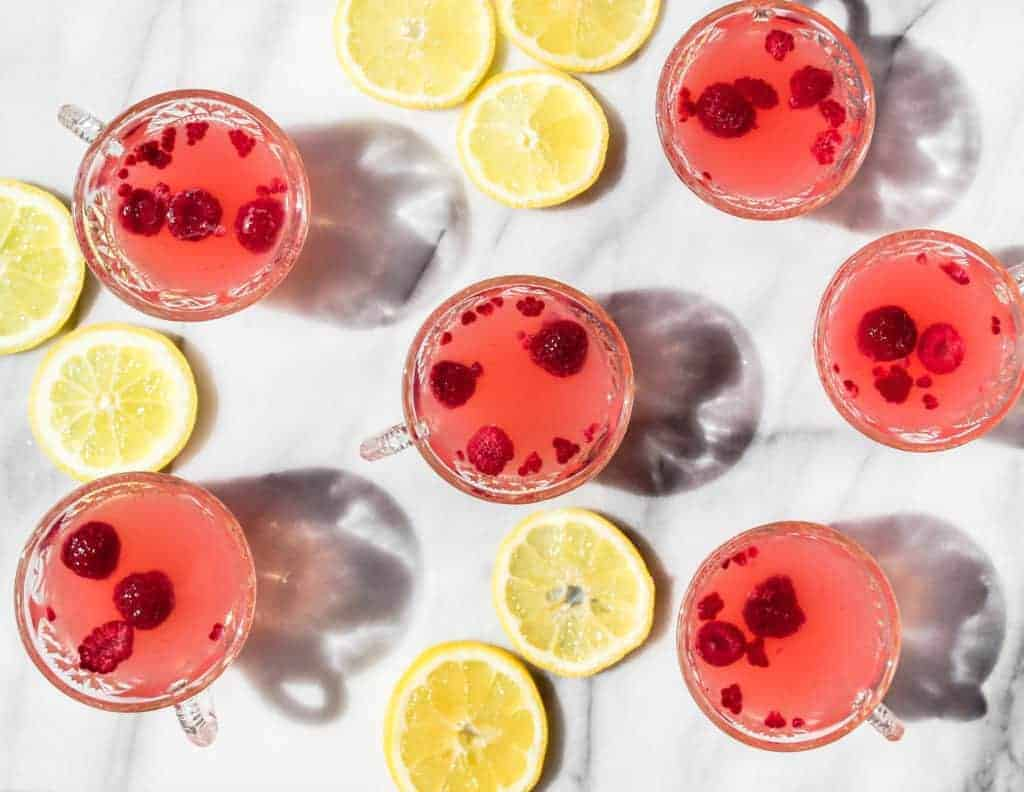 small glass cups filled with pink sparkling lemonade punch with slices of lemon on a marble backdrop