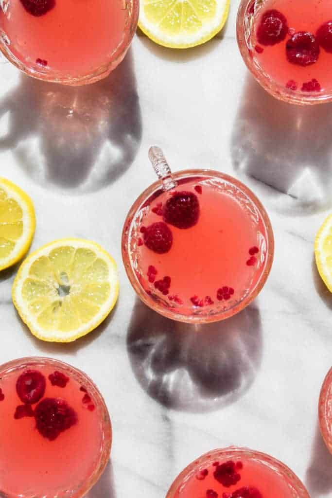 two raspberries floating in a small glass of sparkling raspberry lemonade punch with slices of lemon