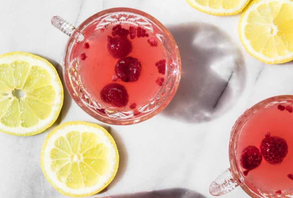 two glass cups with handles filled sparkling raspberry lemonade punch with lemons