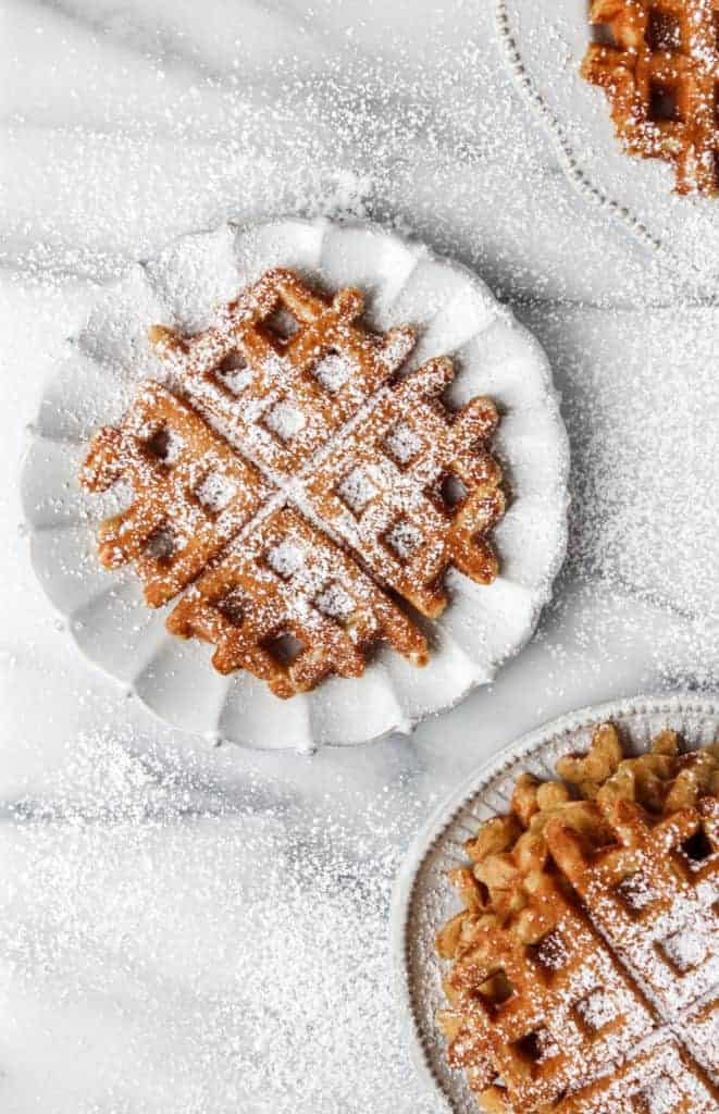 orange pumpkin waffles on white plate on marble background dusted with powdered sugar