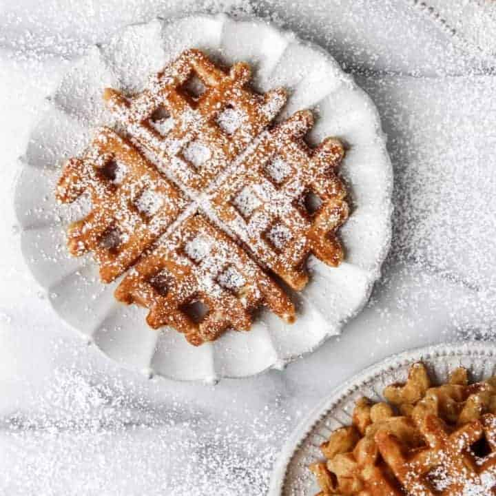 pumpkin waffles on plates with powdered sugar