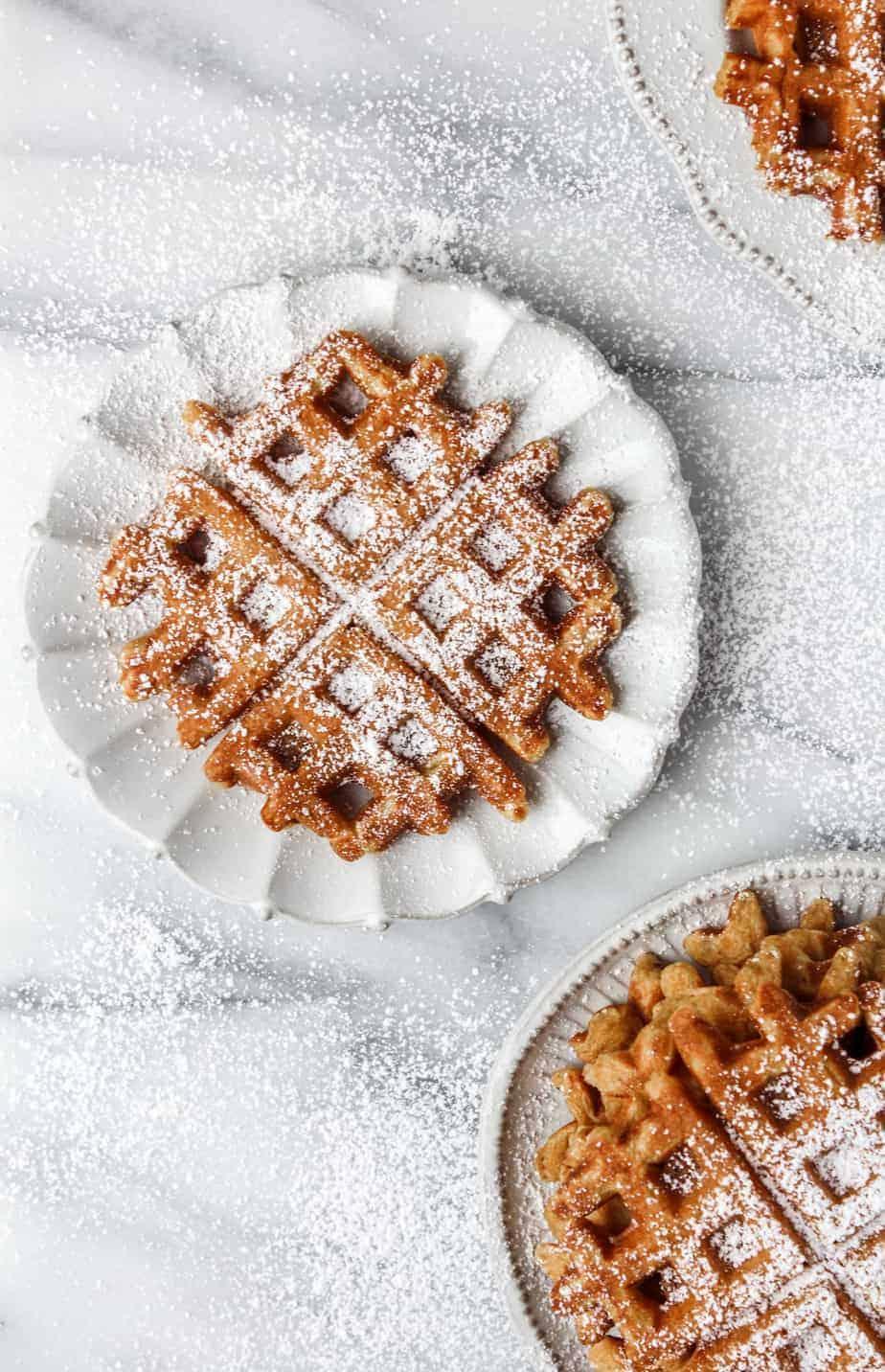pumpkin waffles on plates with powdered sugar