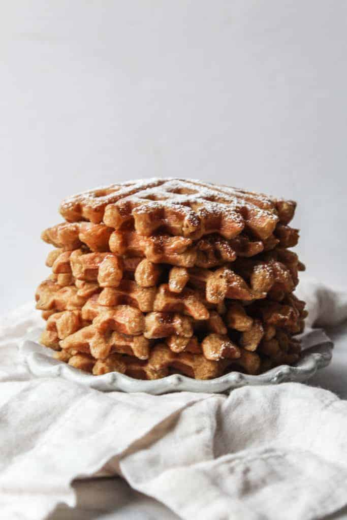 easy pumpkin waffles stacked on a white plate and napkin and topped with powdered sugar