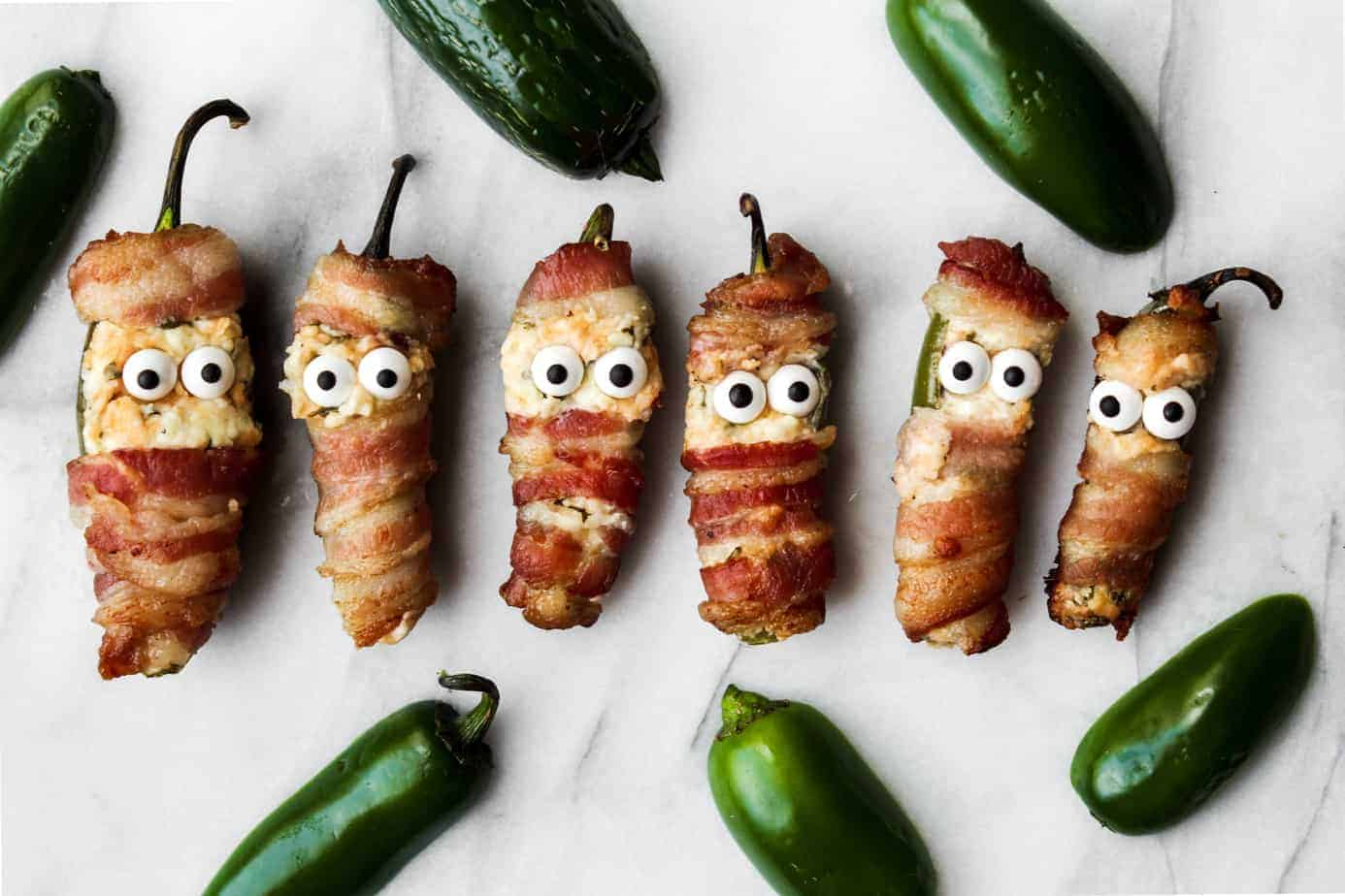 bacon wrapped jalapeno popper mummies in a line