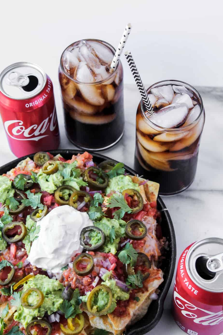 loaded grilled nachos with ice cold coke with straws