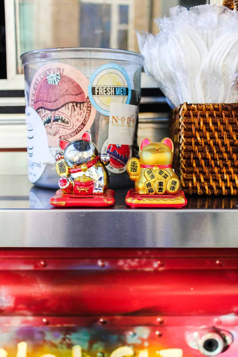 utensils and small cat statutes at the dumpling lady food truck