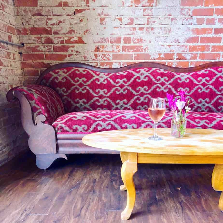 glass of rose wine on a coffee table with pink couch at lincoln's haberdashery
