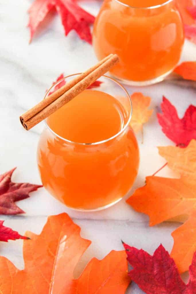 glass of spiked apple cider orange liquid topped with a cinnamon stick on a marble background with red and orange leaves
