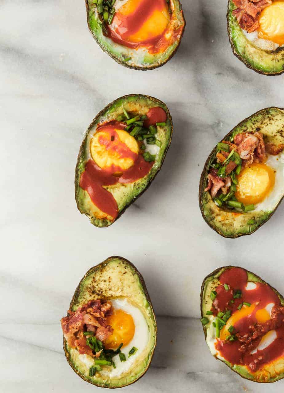 baked eggs in avocado topped with whole30 compliant hot sauce