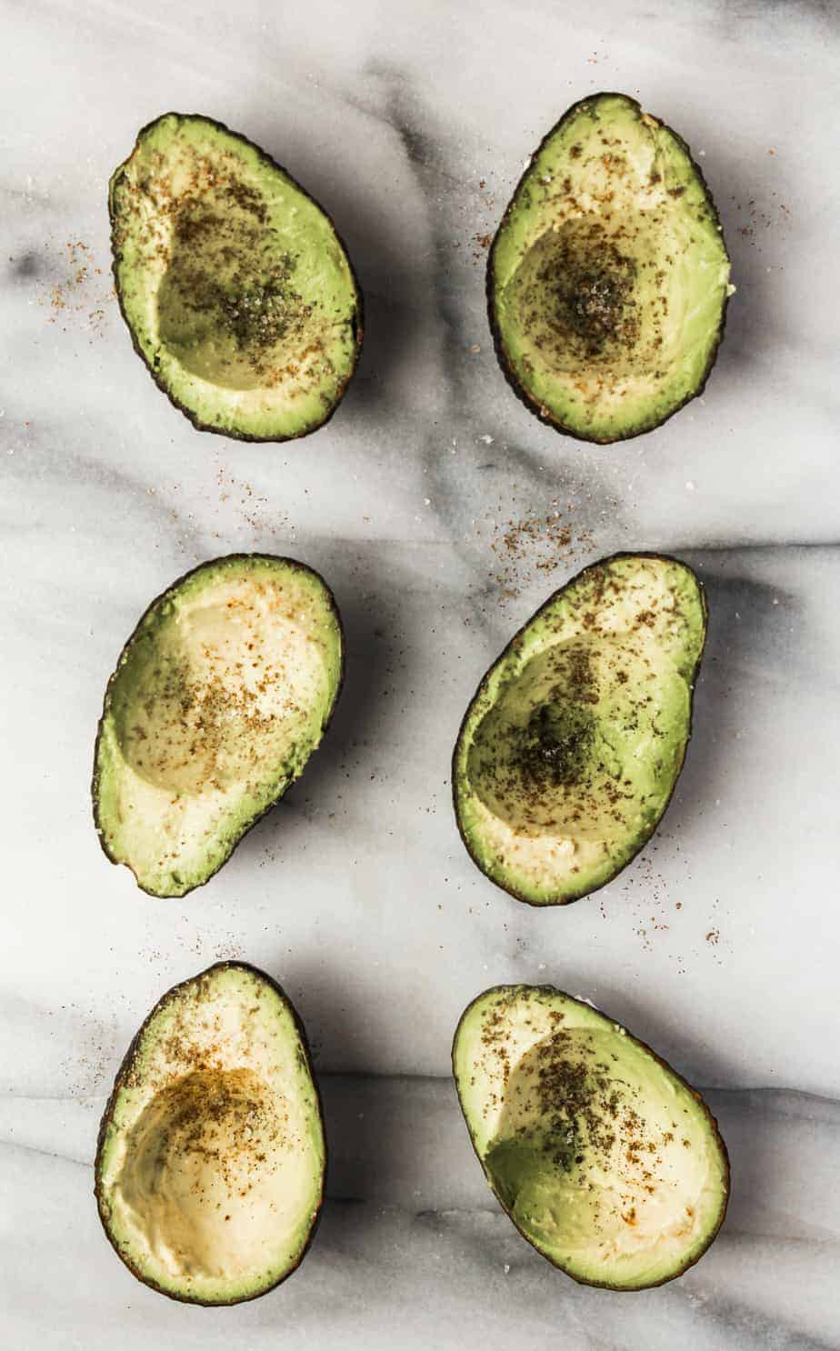 avocados on a marble board with the pits scooped out seasoned with salt and pepper
