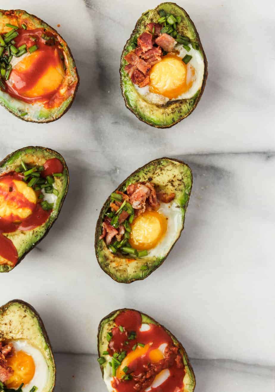 baked eggs in avocados on a marble platter with bacon, chives and hot sauce is an easy whole30 breakfast idea