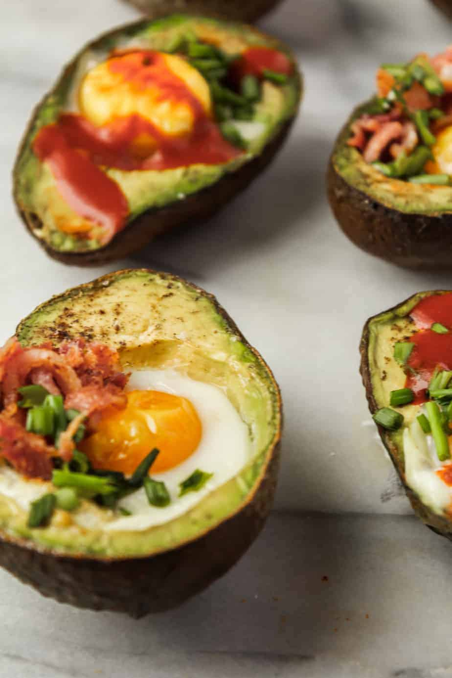 close up shot of baked eggs in avocados topped with bacon, chives and hot sauce