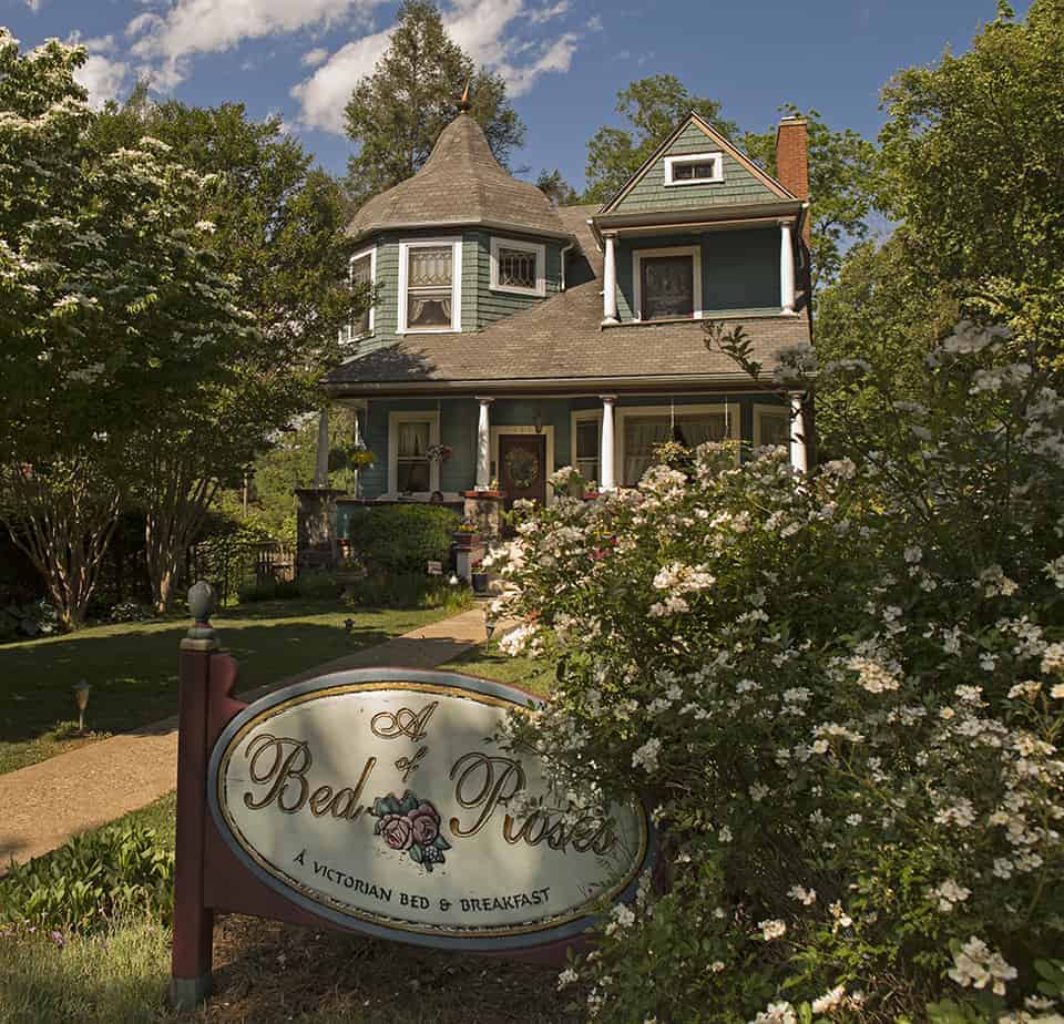 the front of a bed of roses bed and breakfast in asheville nc is painted green with rose bushes