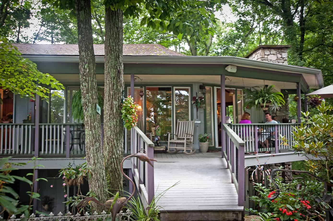 the front porch with rocking chairs and covered by trees at the crooked oak mountain in a bed and breakfast near asheville, nc