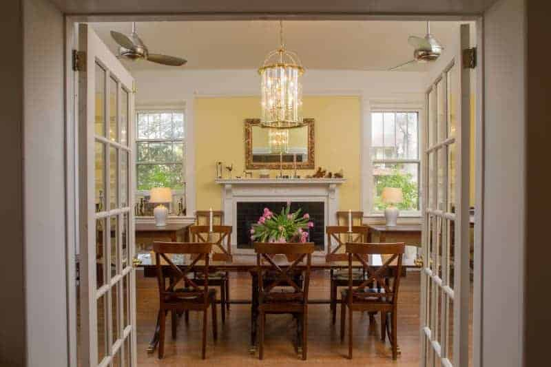 dining room with wood table and chairs with fresh flowers and chandelier at an asheville bed and breakfast
