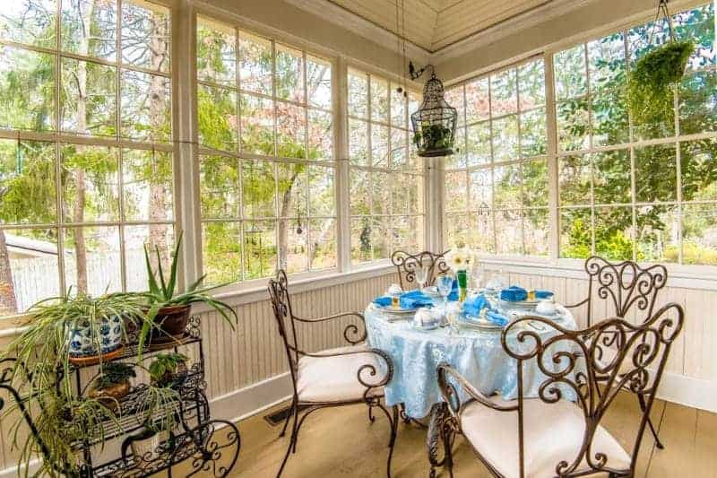 a dining table with a blue table cloth and blue napkins with four chairs in a room full of windows and a plant cart at an asheville b&b