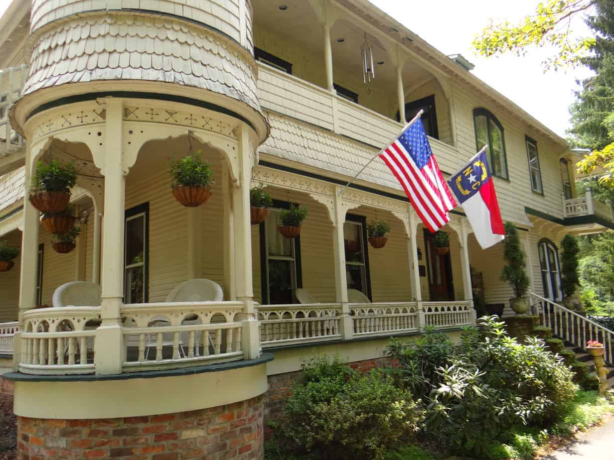 engadine inn and cabins white wrap around front porch with the united states flag and north carolina state flag