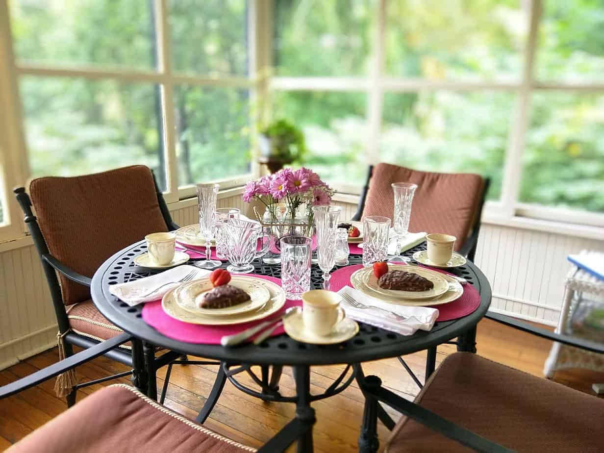 black table set with pink placemats for breakfast with fresh pink flowers at the pinecrest, an asheville bed and breakfast